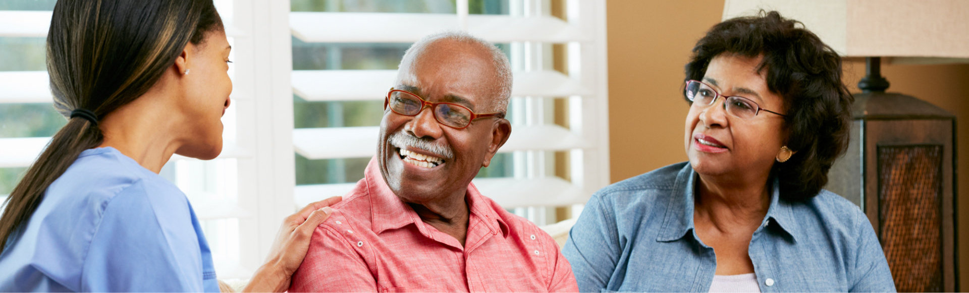 caregiver and elderly couple both smiling
